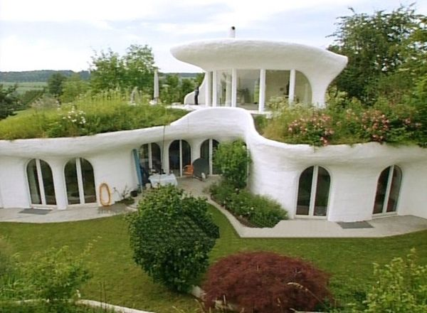 this is called and earthship :) they are very expensive but they all energy beneficent, i think they all come equipped with solar panels and other things that make paying utilitys cheap as hell. I think its a cute little house though with the little grass roofs :) id feel like a smurf or something if i lived here. Which i wouldn't mind at all