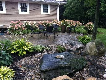 Bubbling rock, stone patio, green grasses, flowers, hostas, traditional modern mix. Completed by Leaf Garden Design Inc.  | oakdale Rd