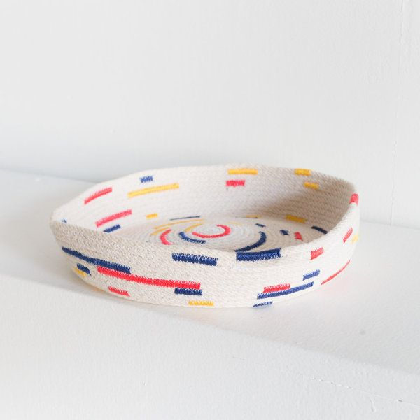 This tray-shaped basket gives a nod to the Bauhaus with it's primary color scheme and circular patterns. Made by hand so each tray will have slight variations. This tray stretches about 9 inches in diameter and is just under 2 inches in height. Ships in 1-2 weeks.