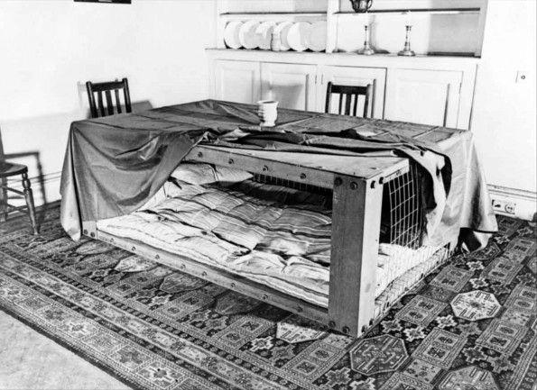 A photograph of a Morrison shelter in a room setting, showing how such a shelter…