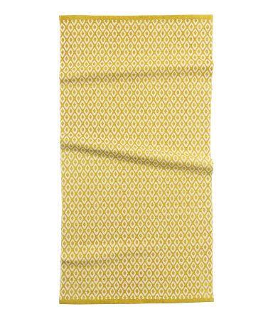 En rektangulär matta i vävd bomullskvalitet med tryckt mönster på ovansidan.