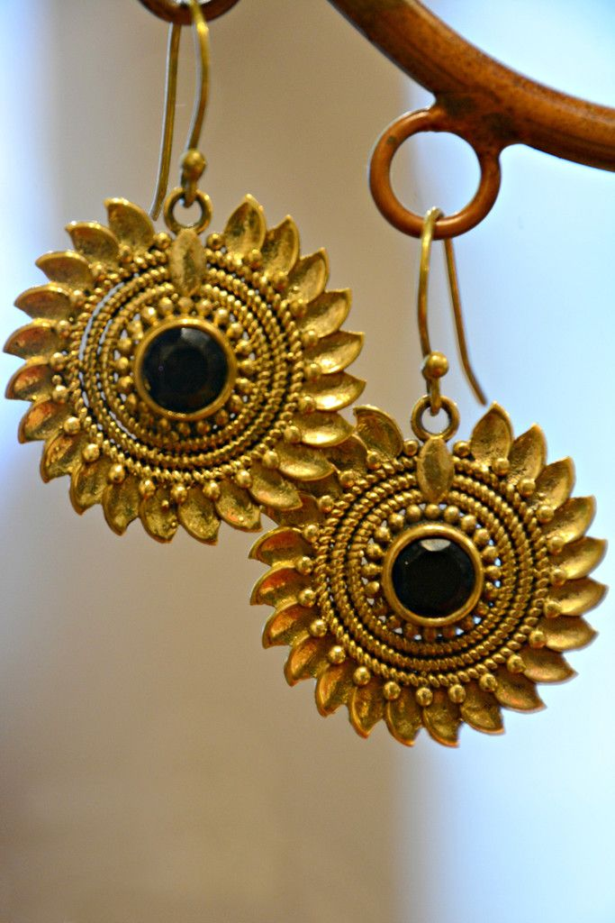 Our Fair Trade Radiant Sunflower Earrings will add a punch of flower power to your outfit. A take on the traditional intricate metal work and mandala motifs found in Indian jewelry, with a faceted black glass bead in the middle of the flower to catch the light.