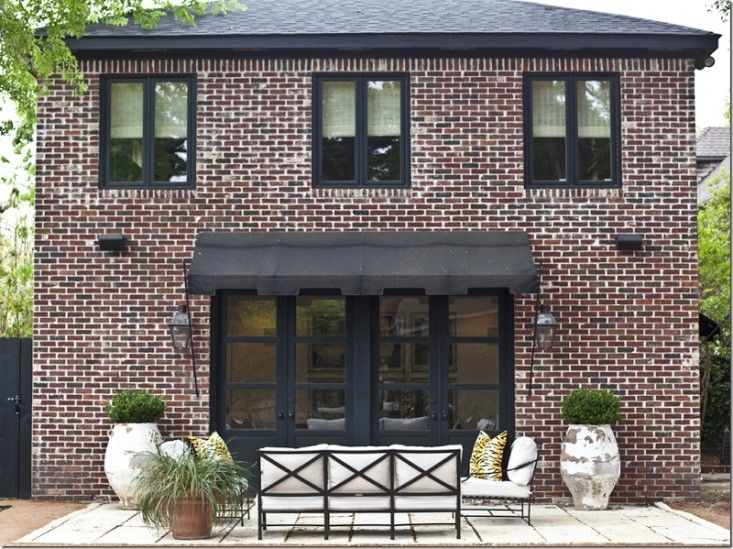 A black Spear Awning with an exaggerated Greek key valence was installed above the doors of Houston designer Mary Jane Gallagher's guest house, at a cost of about $2,200. For more information, see W.K. Hill Awnings.