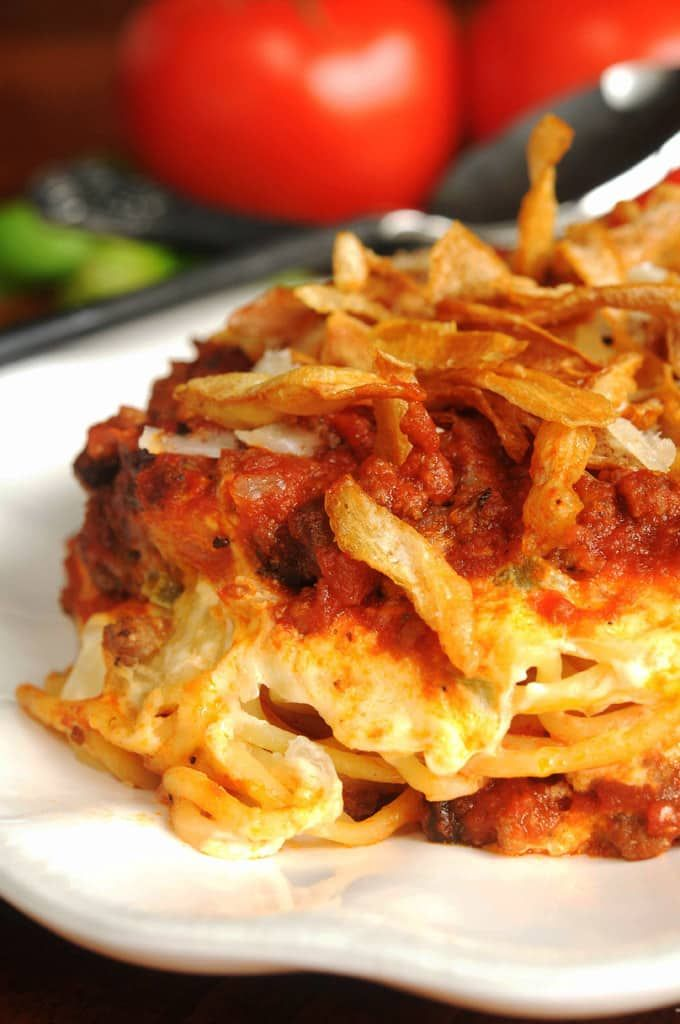 Layered spaghetti casserole topped with french fried onions.