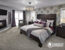 Master bedroom. Two-sided fireplace, beautiful wallpaper, and a sparkling chandelier. | The New Hampshire model by Kimberley Homes, Edmonton, AB #interiordesign #newhomedesign #homedesign #newhome #customhome #yegre #buildwithkimberley #kimberleyhomes #bedroominspo #bedroomideas #bedroom #masterbedroom #wallpaper #fireplace #purple #damask