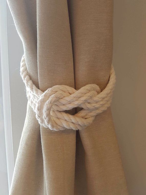 These lovely curtain tiebacks are made of white/ ivory cotton rope.  Cotton rope - 3 Strand construction. Soft to touch, will not shrink or swell when wet.  The tiebacks are sold in pairs and singles. For custom sizes, please get in touch. ORDERING LARGE QUANTITIES? Please, get in touch with me if you wish to purchase more than 2 pairs of curtain tiebacks, so I can calculate the correct shipping cost for you.  Care Instructions : Wipe using damp cloth and allow to air dry. Do not wash. Wall…