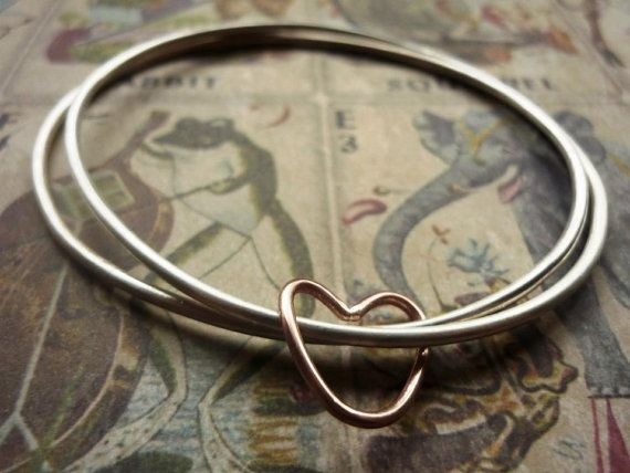 These gorgeous simple sterling silver bangles are handmade to measure. They are simple for everyday wearing and are finished off with this cute little copper loveheart. A perfect gift for the love of your life!  You can choose from one of the sizes below, the most common size being 7cm in diameter. For information about measuring for your bangle please see my policies.  If you do order the bangle in the wrong size, dont worry its not a problem. However there is a charge for re-sizing a…