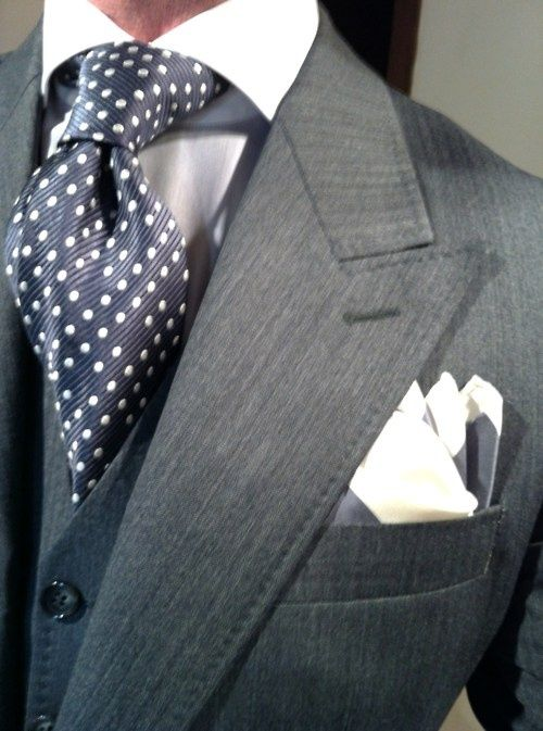 Nail that dapper look with a charcoal blazer and a navy waistcoat.  Shop this look for $370:  http://lookastic.com/men/looks/blazer-and-pocket-square-and-tie-and-dress-shirt-and-waistcoat/1764  — Charcoal Blazer  — White Silk Pocket Square  — Navy Polka Dot Silk Tie  — White Dress Shirt  — Navy Waistcoat