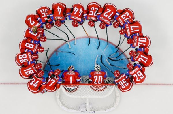 Image: The Russian women's ice hockey team huddles around the net before their game against Germany at the 2014 Winter Olympics, Sunday, Feb...