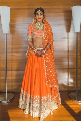 Bridal Lehengas - Karan & Aastha | WedMeGood | Bride in an Orange Lehenga with White Borders and Golden Embroidery Outfit by: Anita Dongre #wedmegood #indianbride #indianwedding #bridallehenga #lehenga #orange #anitadongre