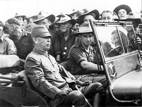 A jeep carrying a Japanese general pauses in front of a group of Australian soldiers during the surrender of Japanese forces in New Guinea.