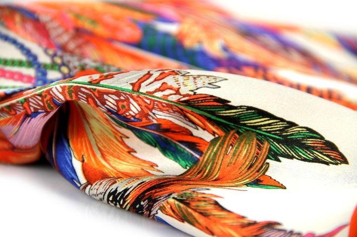 De couleur orange flashy, ce foulard carré en soie se démarque par ses motifs originaux de plumes