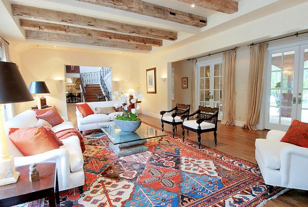 Neutral furnishing and a colorful rug are perfectly combined. Wooden beams look excellent