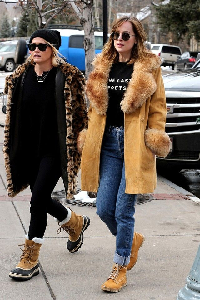 Dakota Johnson wears a suede fur-trimmed coat, Bella Freud sweater, high-waisted jeans, round sunglasses, and Timberland boots