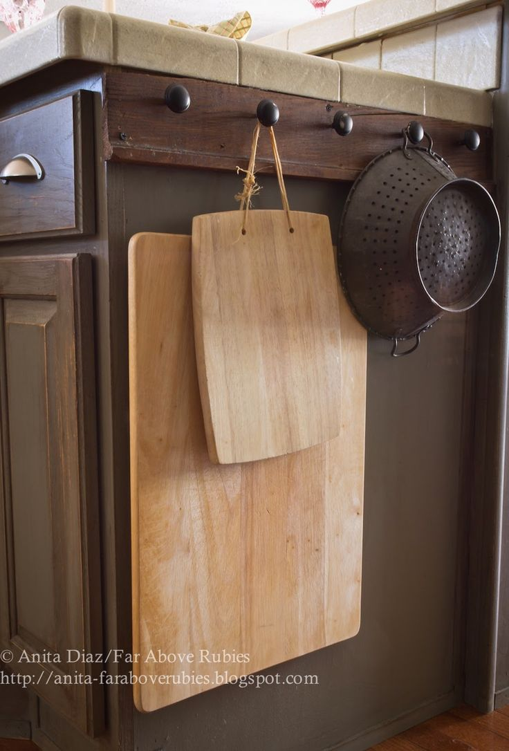 Heavy, clunky kitchen tools, like cutting boards and colanders, fit awkwardly into cabinets — so why not hang 'em on the outside instead? This way they'll be easy to grab and put away. See more at Far Above Rubies »   - HouseBeautiful.com