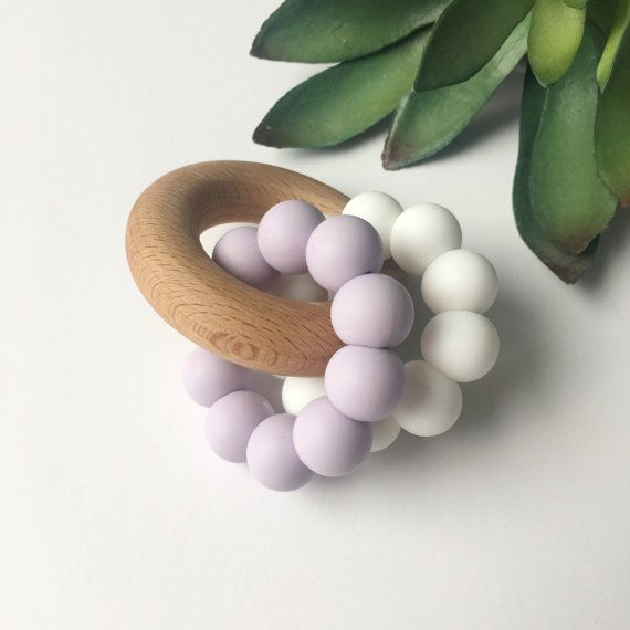 These beautiful handmade DUO teethers are the perfect size and shape for little hands to grasp, and the perfect combination of soft and smooth textures for budding teeth and sore gums! The double silicone ring gives your little one the chance to practise their grasping and coordination skills at the same time as soothing their gums. Our teethers are made from non-toxic, food grade silicone beads that are BPA, Lead, Phthalates, Latex, and PVC free. They are interlocked with organic beech…