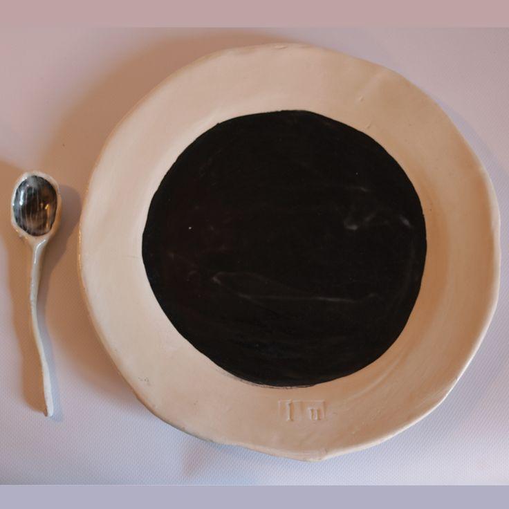 """Il piatto rotondo (o ovale) in ceramica è fatto a mano e rientra nella linea """"A Tavolaaaaaa"""" della designer Lucia Cavalli. Materiali: terraglia bianca, ingobbio nero e cristallina."""