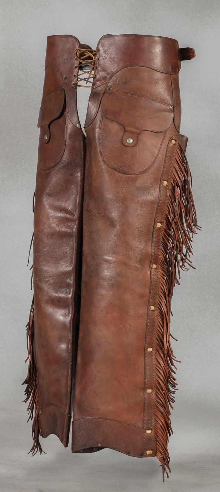 """Rare F. J. Villaescusa Marked Chaps. Early Territorial marked shotgun chaps. Laced sides and full length fringe with outside pockets. Well-marked with the scarce cartouche """"F.J. Viilaesusa - Tucson A.T."""""""