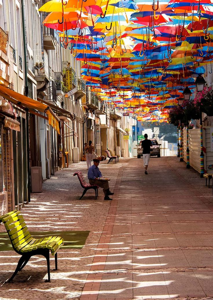 Not only does this installation add vivid colours to the streets of Agueda in Portugal, it also provides shade! Floating Umbrellas by Sextafeira in Portugal #installation #art