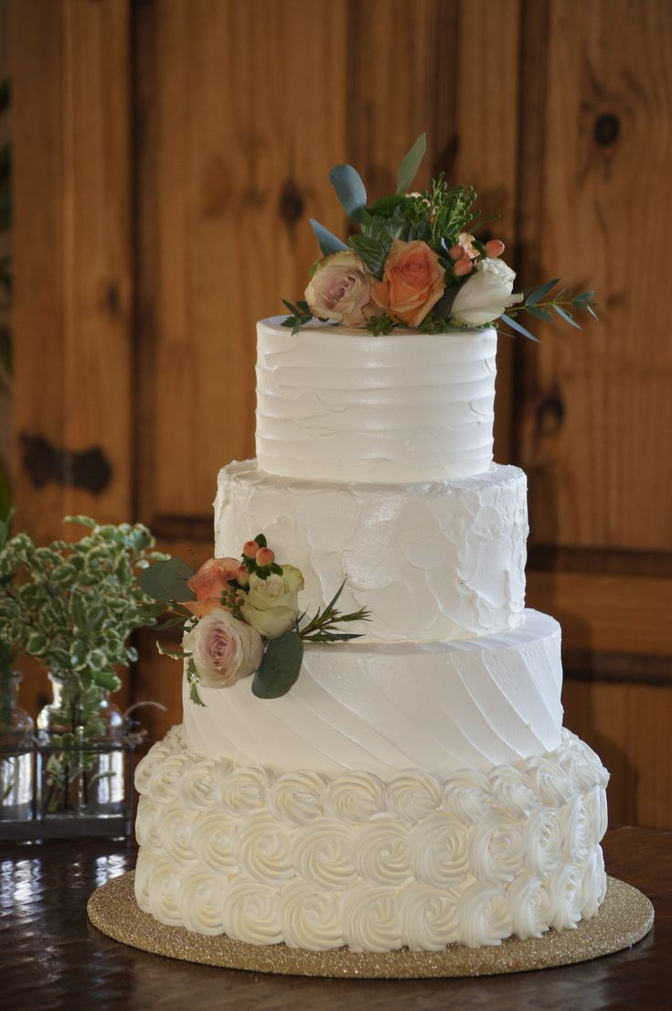 Tiered white wedding cake with rosette and textured spackle design topped with roses