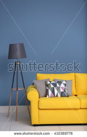 Free Yellow sofa and multicoloured pillows on a blue wall ...