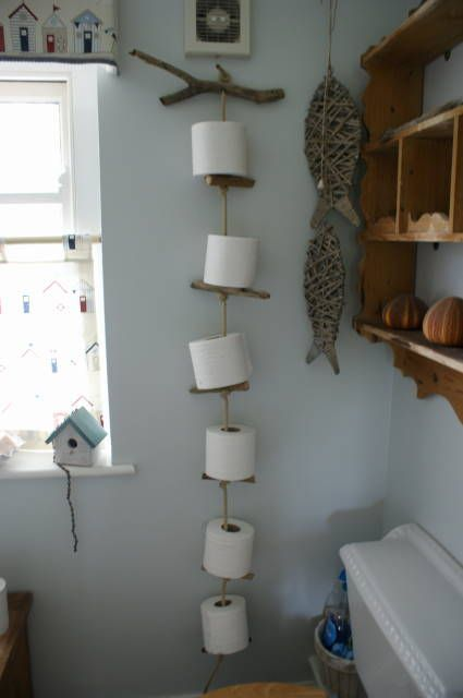 Toilet paper holder made of driftwood and old rope. just turn the wood barrel