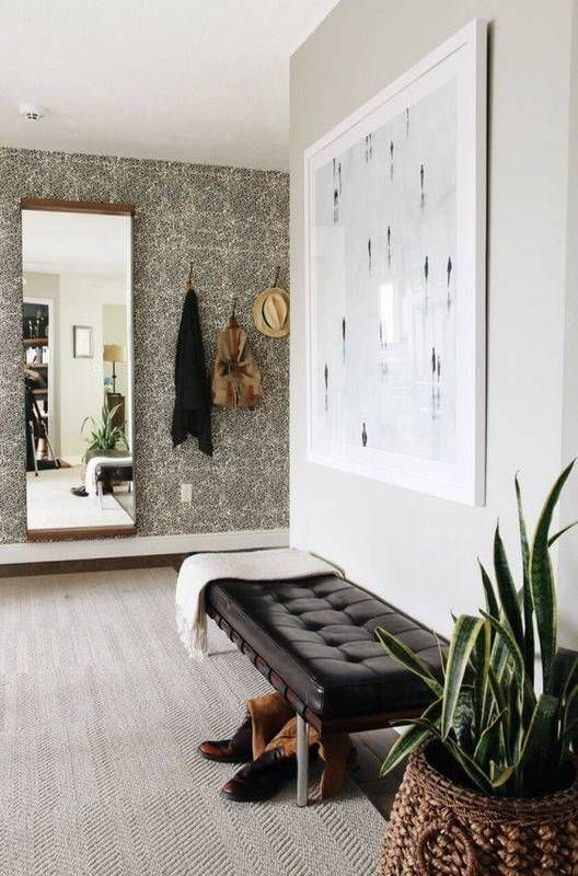 Minimalist entryway with a gray wall, a contrast wallpaper, large art, and a bench ottoman