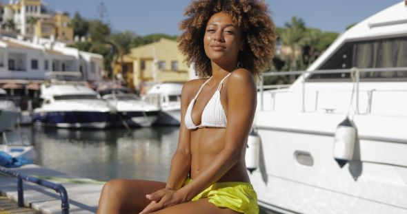 Wonderful Fit Woman on Seashore by Daniel_Dash Beautiful young girl in bikini sitting on wooden pier looking cheerfully at camera on background of yachts in tropical bay.