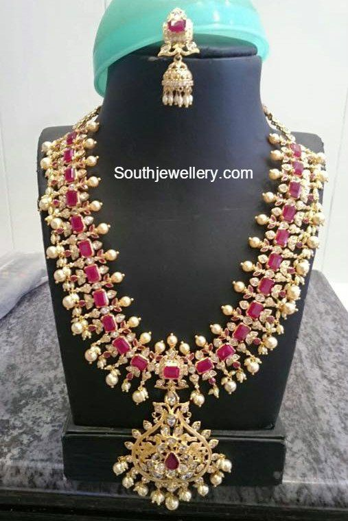 22 carat gold bridal haram and jhumkas adorned with rubies, cz stones, small pearls and south sea pearls. Related PostsCZ Ruby Necklace and Haram SetCZ Stones HaramCZ Stones Necklace and HaramAntique Ruby Long ChainCZ Mango Kasu Necklace and Haram SetCZ Stones Peacock Haram