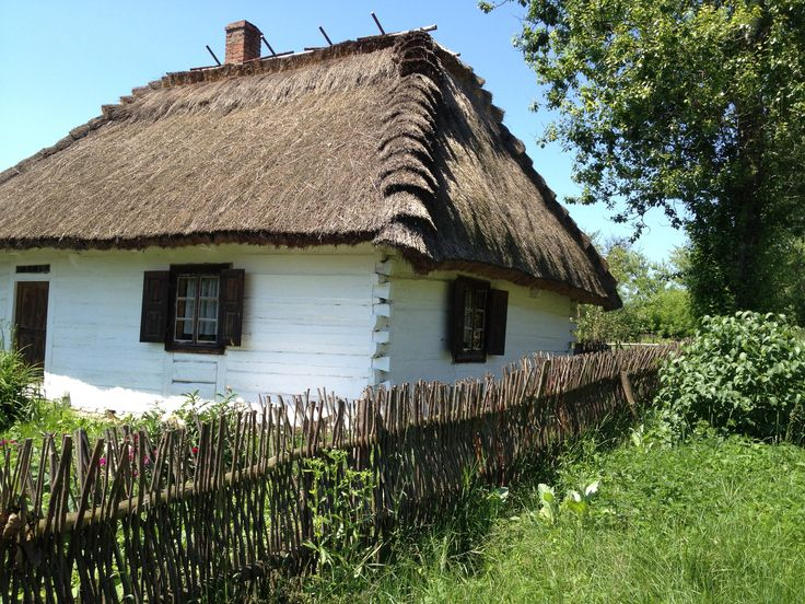 Traditional Polish home with a hay roof, wood structure and stick fence.