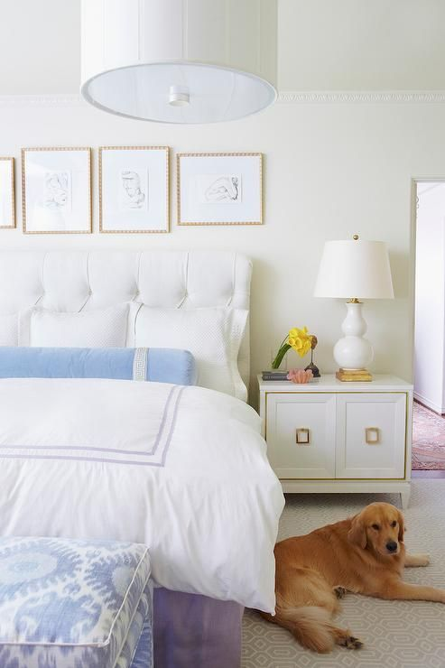 Lovely bedroom features  collection of abstract sketches over a white tufted headboard on bed dressed in white and purple hotel duvet, blue Greek key bolster pillow as well as a purple bedskirt next to a white and gold cabinet as nightstand topped with a white and gold lamp, E.