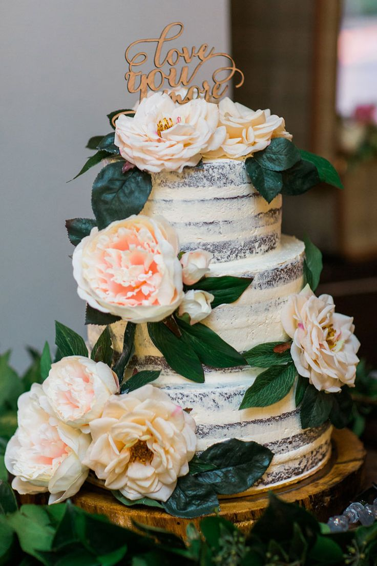 "Semi naked three tier wedding cake with pink roses and ""Love You More"" wooden topper 