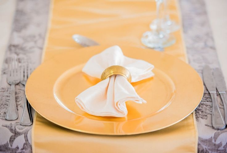 Monte Vista Venue gold under plates with a white damask napkin and a gold napkin ring for a pink and gold wedding