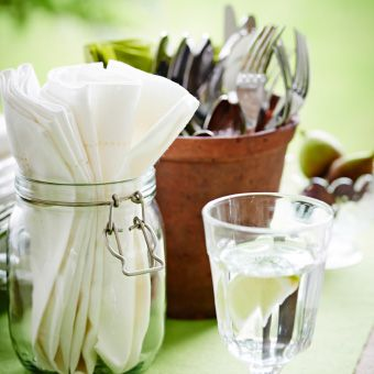 Close-up of wine glass, white napkins in glass jar and terracotta pot filled with cutlery.