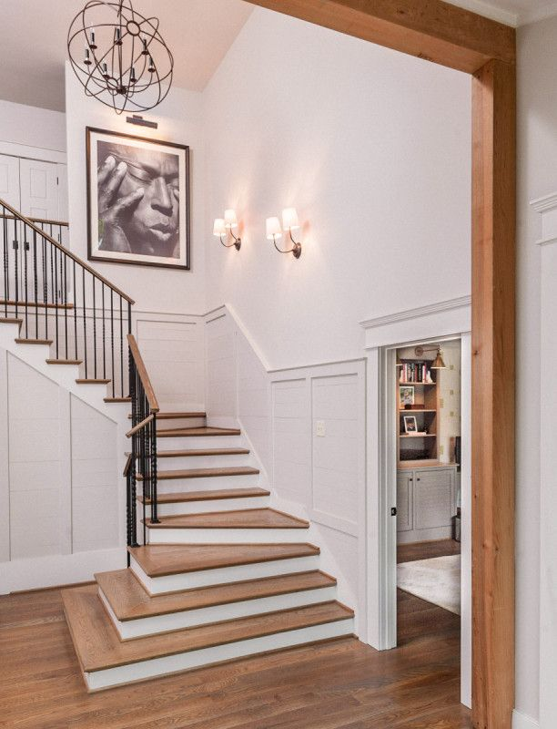 The home entrance opens onto a spacious foyer with a grand staircase. Christopher Architecture and Interiors