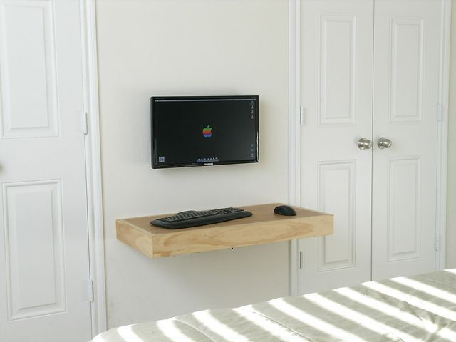 An ultra minimalist office: ...a tiny floating desk with nothing but a screen, keyboard and mouse.