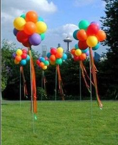 balloon topiary -- no tutorial, but looks like they used inexpensive poles (Lowes), and bunched non-helium balloons together (yea! saves time & money without the helium), and then added ribbon.  Inexpensive, secure, and no issues with helium balloons running a-muck & getting tangled.  It's also long-lasting.