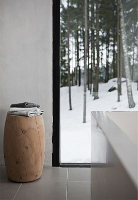This beautiful and understated house belongs to Finnish designer Ulla Koskinen. It is one of our dream homes. Earthy tones of timber and a paired back palette of warm neutrals creates a look that's clean but cosy. Natural materials such as the timber benchtop in the kitchen and the rough concrete walls lend the house an organic quality - a subtle, refined rustic appearance that befits this beautiful woodland home. Including the Offcut Stool from Tom Dixon Studio.