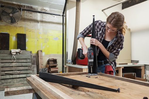 Woman installs legs on wooden table