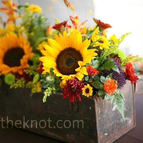 """A little more """"country,"""" this centerpiece is really nice with the sunflowers (one of my favorites). Nice and wild looking. Also, the container is really lovely."""