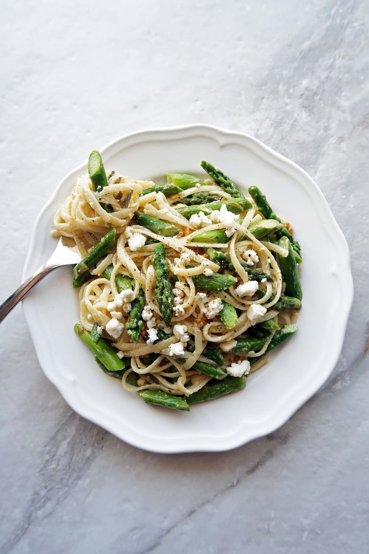 Lemon Feta Linguine with Garlic Asparagus on a white plate with linguine twirled around a fork.
