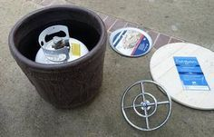 A flower pot big enough to hold a propane tank, a circular wooden table top, a pizza pan and a fire pit kit are needed to make a portable backyard propane fire pit.