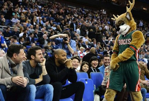 14-15NBA、ミルウォーキー・バックス(Milwaukee Bucks)対ニューヨーク・ニックス(New York Knicks)。ミルウォーキー・バックスのチームマスコットと交流するサッカー元フランス代表のティエリ・アンリ(Thierry Henry)氏とチェルシー(Chelsea)のセスク・ファブレガス(Cesc Fabregas、2015年1月15日撮影)。(c)AFP=時事/AFPBB News