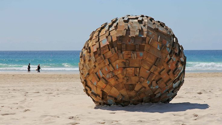Giant wooden spheres symbolising relics from the lost city of Atlantis dot the beach as part of the Swell Sculpture Festival on the Gold Coast. (Photo: ABC/Damien Larkins.)
