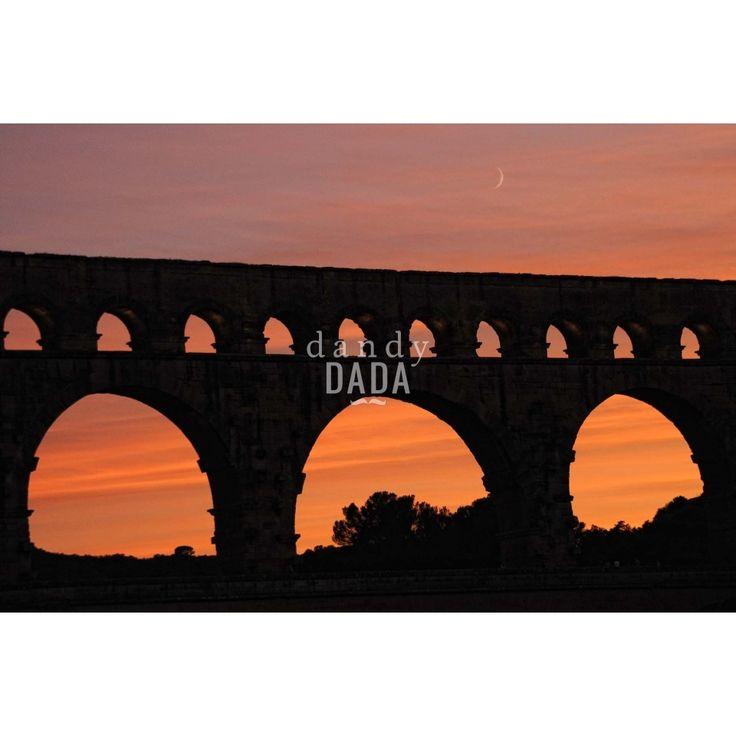 """L'opera  """"Pont du Gard"""" di Piergiorgio Pirrone appartiene alla collezione """"Sunset"""". Perfettamente integrato nel contesto naturalistico della Provenza, l'acquedotto romano del I secolo a.C. sembra perdere tutta la sua imponenza architettonica alle prime luci del crepuscolo."""