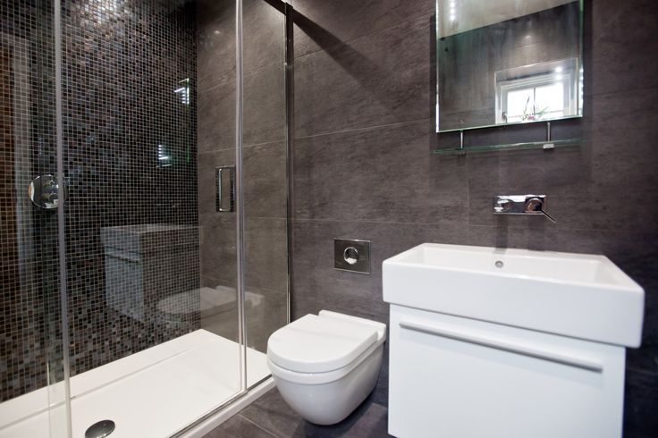 Black ensuite with large floor and ceiling tiles and black mosaics creating a feature wall. Copyright The Designer Knowledge. Photo by Ani Evans Photography.
