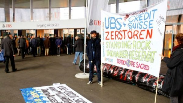 Protesters display a banner to protest against the financing of the Dakota Access oil pipeline by Swiss banks UBS and Credit Suisse as participants arrive ahead of the annual shareholder meeting of Swiss bank UBS in Basel, Switzerland. | Foto: Reuters