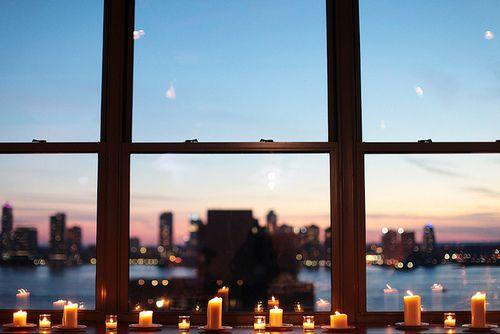 Candles in front of an amazing set of windows.