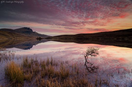 Sunrise from loch Fada, Isle of Skye, Old man of Storr reflects in the distance