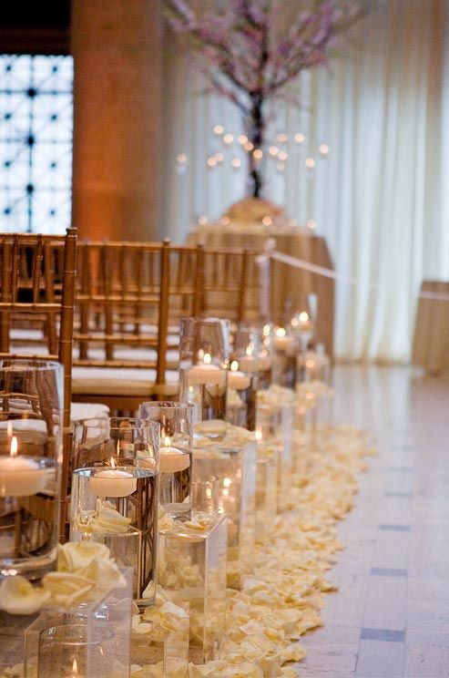 White and cream rose petals surround hurricanes that line the aisle.
